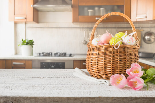 Easter wicker basket with painted eggs and tulips on kitchen white wooden tabletop. Spring composition. Space for text or design.