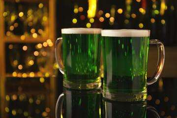 Glasses of green beer on black table against blurred lights. St Patrick's Day celebration