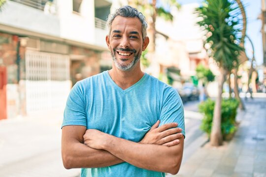 Middle age grey-haired man wearing casual clothes at street of city happy face smiling with crossed arms looking at the camera. positive person.