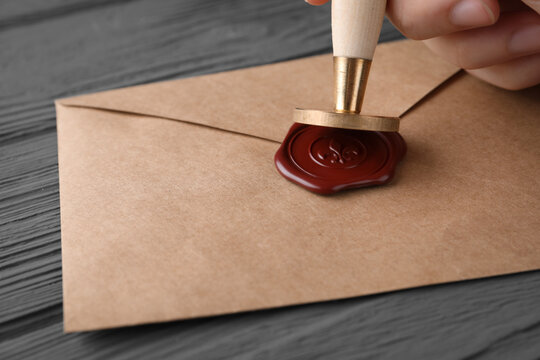 Woman sealing envelope at black wooden table, closeup