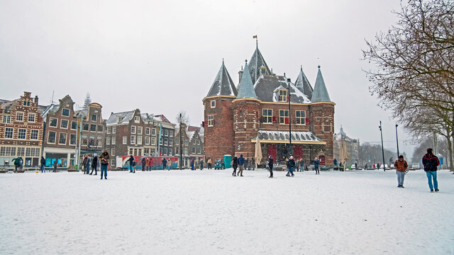 Traditional snowy Waag building at the Nieuwmarkt in Amsterdam in the Netherlands in winter