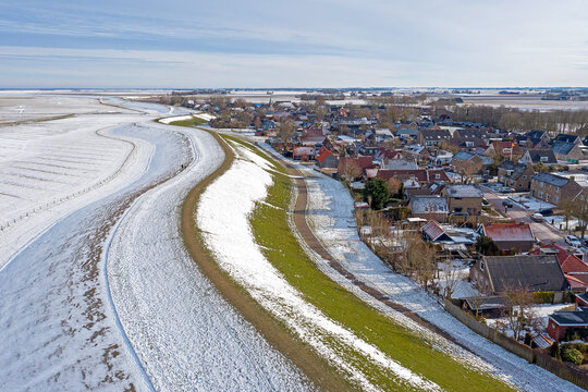 Aerial from snowy village Moddergat in Friesland at a frozen Waddensea in the Netherlands