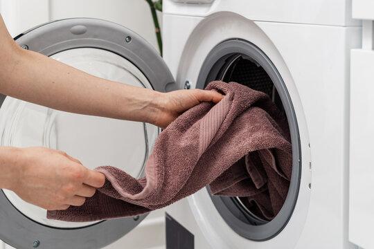 Woman washing laundry using modern automatic machine