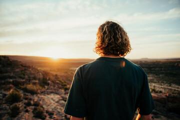 Fototapeta Caucasian male free spirit walking through wilderness embracing sunrise