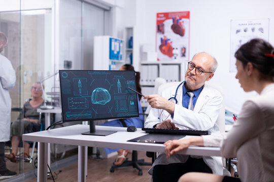 Senior physician showing scan body result to young patient pointing with pancil on desktop. Doctor and woman discussing in front of pc about brain functions, medical consultation in hospital clinic