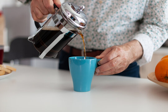 Close up of elderly man hands pouring coffee in cup during breakfast sitting in modern kitchen. Elderly person in the morning enjoying fresh brown espresso from vintage mug, filter relax refreshment