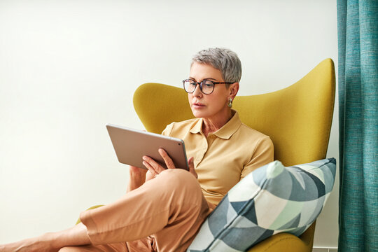 Stylish senior woman holding a digital tablet while sitting in living room