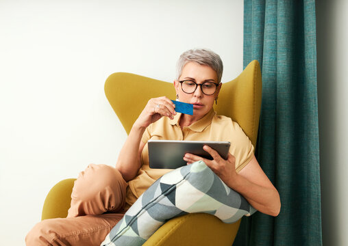Woman shopping online in living room. Mature woman with credit card and digital tablet at home.