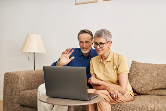 Senior couple using a laptop for video call. Mature man greeting with a hand wave while looking at a laptop.