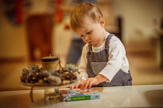 Little child  playing with a storybook on the table by the decoratives