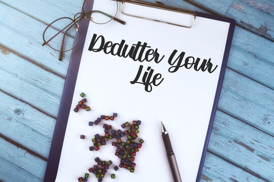 Selective focus image of spectacle glass and pen with declutter your life on a wooden background.