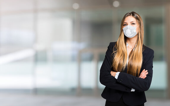Portrait of a young masked businesswoman, covid coronavirus concept