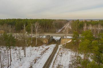 Tory kolejowe w lesie zimą.