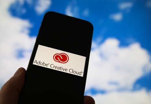 Viersen, Germany - February 9. 2021: Closeup of smartphone with logo lettering of adobe creative cloud computing provider service, blurred sky and cloud background