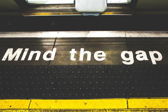 Mind the gap sign underground. Safety concept.