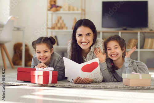 Mother's Day. Portrait of a happy mother with a postcard in her hands lying on the floor with her daughters among the gifts. Concept of women's day, mother's day, family and love.