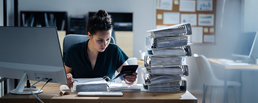 Young Businesswoman Working At Office With Stack Of Folders