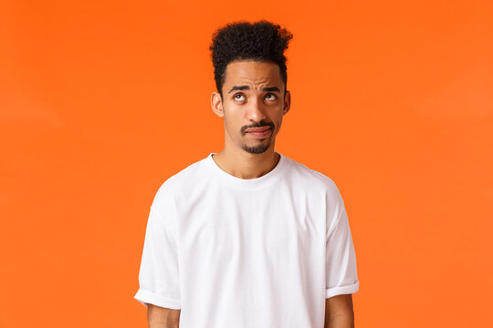 Indecisive and skeptical, gloomy african-american hipster guy with moustache, afro haircut, smirk and looking up unsure, having doubts, dont know how act, standing orange background