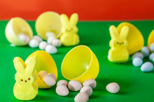 Easter egg hunt concept made with crisp sugar shell coated chocolate eggs and marshmallow easter bunnies. Three little bunnies  with small sweet eggs coming out of bigger ones on green surface.