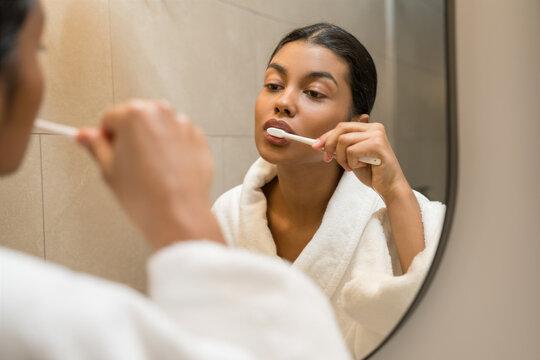 Woman wearing white bathrobe brushing her teeth
