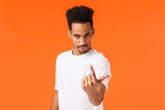You come here now. Serious bossy and strict, confident man with angry expression, frowning looking under forehead and flick index finger as if inviting, demand person step foward, orange background
