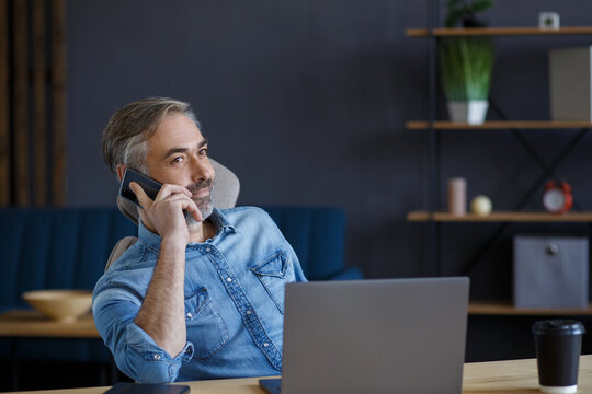 Senior grey-haired businessman talking on the phone in office. Conversation with business partners. Business portrait of handsome mature man sitting at workplace. Communication, negotiation.