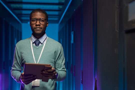 Waist up portrait of African American data engineer looking at camera while working with supercomputer in server room lit by blue light, copy space