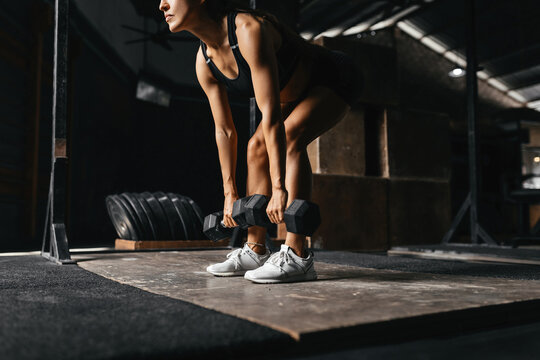 Fit young woman at a crossfit style on dark gray background. Fitness, functional, training, and lifestyle concept
