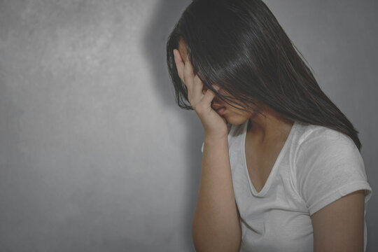 Young woman crying and covering her face useful to illustrate stress, depression or domestic violence