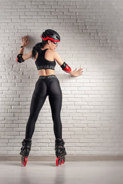 slender woman in sports clothes on roller skates against the wall