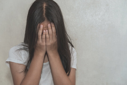Young girl hiding face. Violence against women concept.