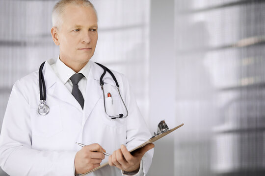 Elderly confident doctor standing straight and using clipboard in clinic. Perfect medical service. Medicine and healthcare concept