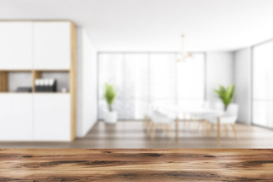 Wooden desk on blurred background of white office room with furniture
