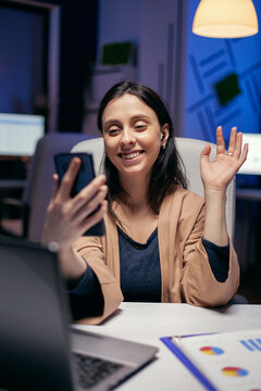 Saying hello in the course of teleconference with entrepreneurs doing overtime. Woman working on finance during a video conference with coworkers at night hours in the office.
