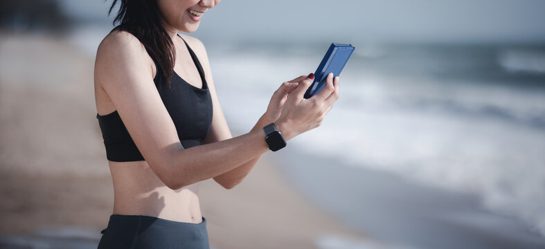 Wellbeing athlete sport concept, Asian muscular healthy woman jogging running looking at smartphone on beach
