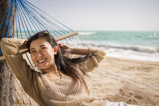 Summer vacations concept, Asian female in casual eyeglasses smiling lying on hammock on beach