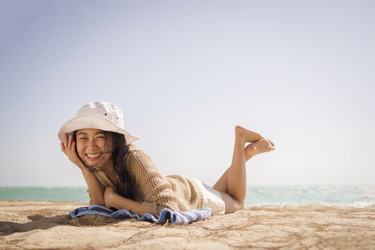 Summer vacations concepts, Portrait of smiley asian long hair female in hat lying on sand beach with sea background