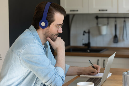 Pensive Caucasian male in earphones look at laptop screen writing studying online on laptop from home. Focused young man in headphones watch webinar, take distant educational training or course.