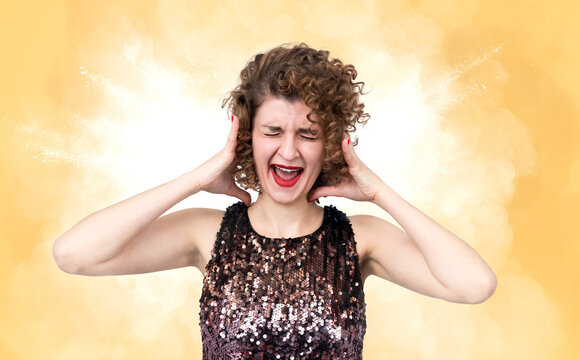 Portrait of a screaming furious young woman with closed eyes and open mouth on yellow smoke background. Conflict and quarrel concept