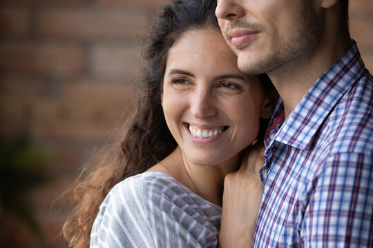 Close up smiling beautiful dreamy woman hugging man, looking to aside, happy young wife visualizing good future with husband, young couple enjoying tender moment, planning, standing at home