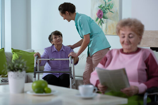 Senior lady reading a newspaper in common room of professional nursing home