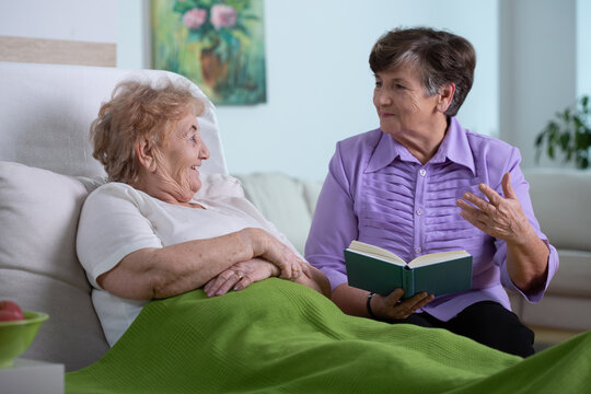 Two senior female friends spending time together in nursing home