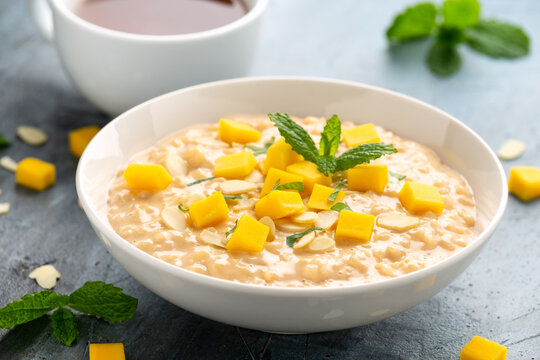 Rice pudding with cinnamon and mango in white bowl