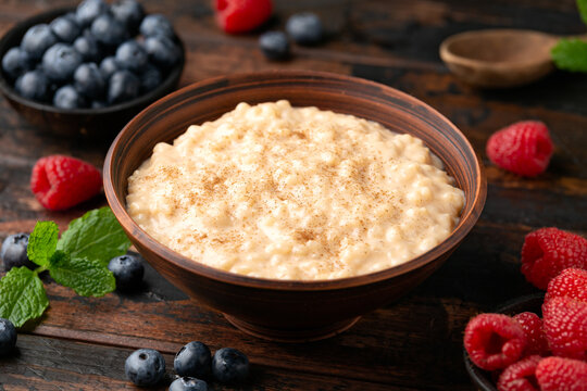 Rice pudding with cinnamon and blueberry, raspberry in rustic bowl
