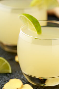Ginger and lemon beer sparkling fizzy drink in glasses with lime wedges on the side
