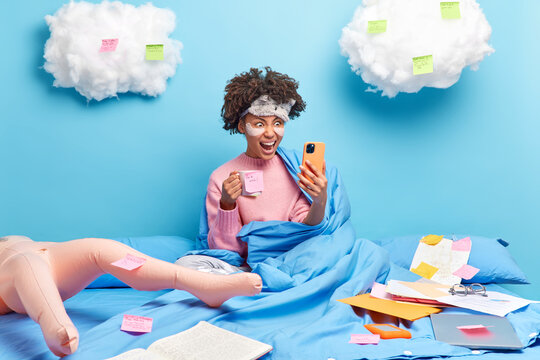 Angry irritated dark skinned woman has video conference shouts loudy at interlocutor works on project from home drinks coffee makes list to do on sticky notes poses in bed with papers around