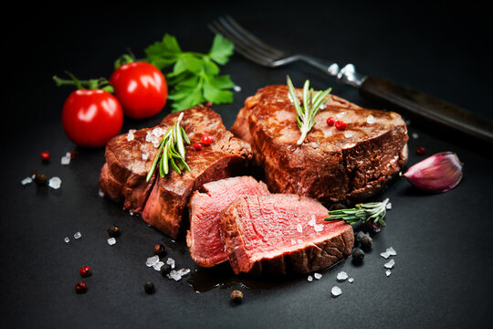 Grilled beef filet steaks with herbs and spices on dark slate