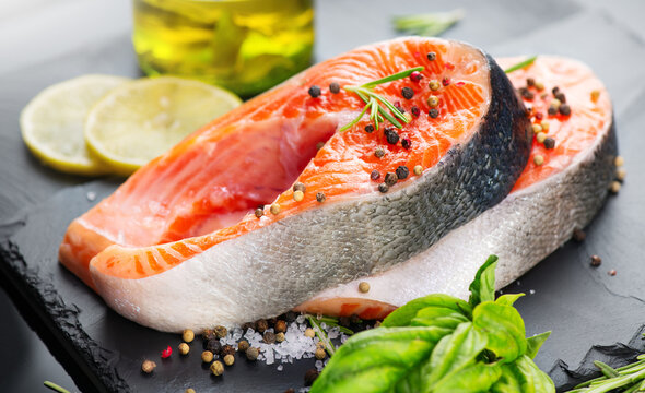 Salmon. Raw Trout Red Fish Steak served with Herbs and Lemon and olive oil on slate. Cooking Salmon, sea food. Healthy eating concept.