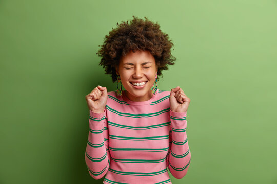 Joyful Afro American woman raises fists anticipates for something good happen feels overjoyed closes eyes with great desire to hear results dressed in casual striped jumper isolated on green wall