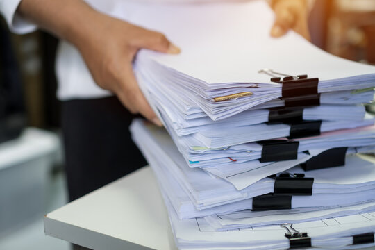 Stacks of lot documents report papers with clips waiting be managed by office workers arranging on desk in busy office. Concept of workload in business finacial paperwork information or investigate
